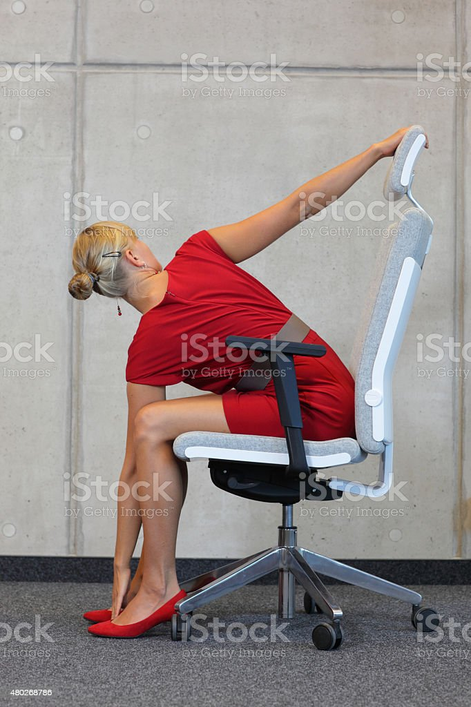 yoga on chair in office - business woman exercising stock photo