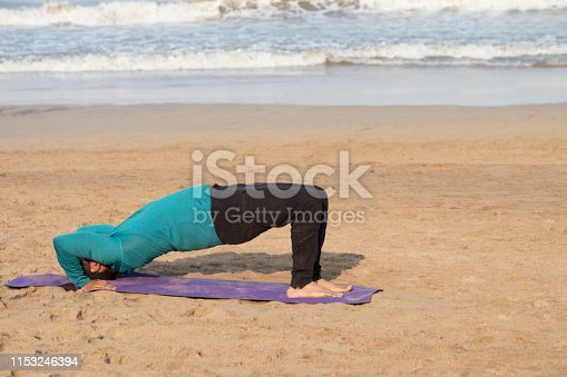 Young man practicing yoga bridge pose on the beach in morning sunlight
