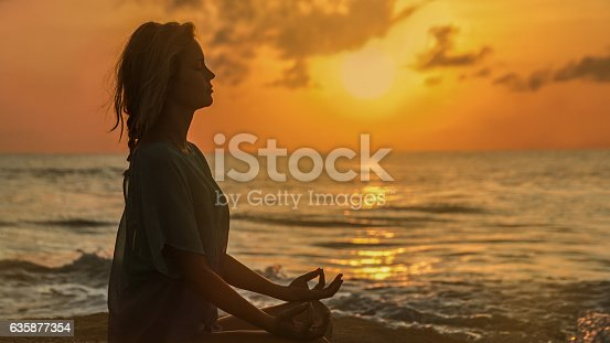 Woman meditating in lotus pose. Sunset, holiday relaxation