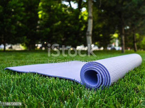 Yoga or fitness Mat. Mat for sports on the green grass in the Park. Exercise in the fresh airYoga or fitness Mat. Mat for sports on the green grass in the Park. Exercise in the fresh air