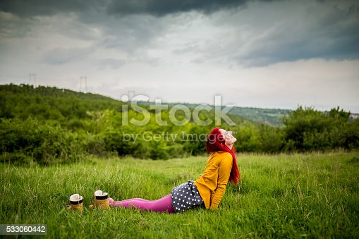 Young redhead doing yoga outdoors