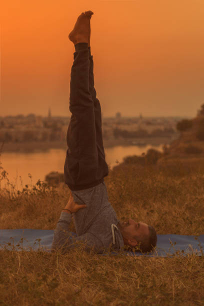 Yoga Man doing yoga on sunset with city view,Salamba Sarvangasana/Supported Shoulderstand.Toned image. shoulder stand stock pictures, royalty-free photos & images