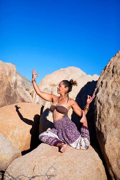 pigeon pose yoga on the rocks - pumphose stock-fotos und bilder