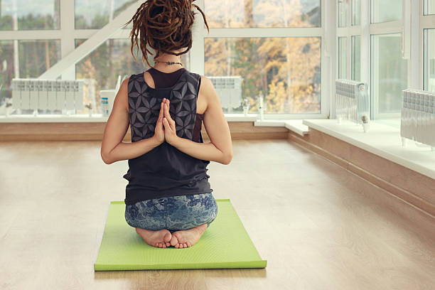Yoga pose. A girl practice yoga in a bright room. stock photo