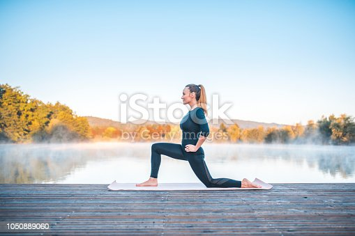 Shot of young woman doing yoga in nature on a misty morning in Ljubljana, Slovenia. Foggy lake is in the back.