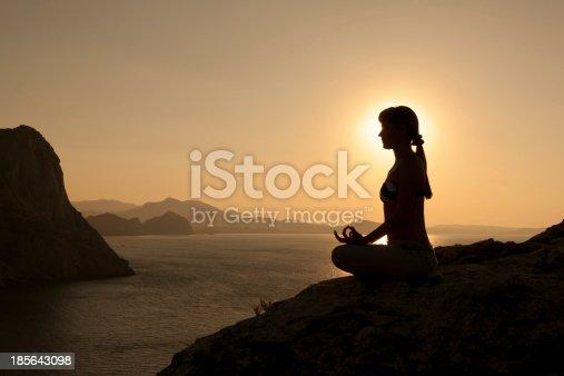 istock yoga pose silhouette at sunrise 185643098