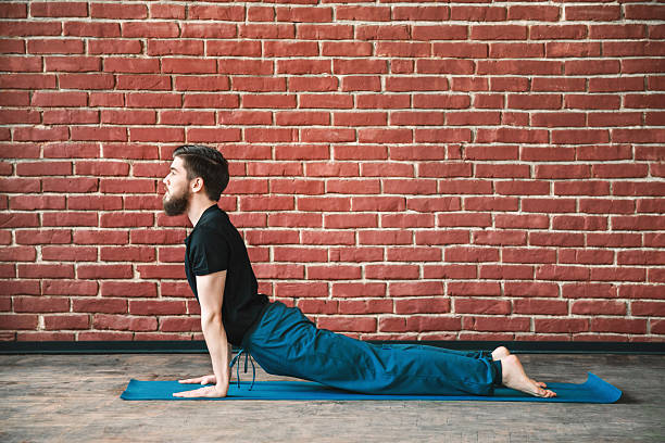 Yoga positions at wall background Young man with a beard wearing black T-shirt and blue trousers doing yoga position on blue matt at wall background, copy space, cobra asana, bhujangasana cobra pose stock pictures, royalty-free photos & images