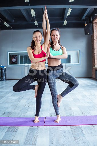 istock Yoga positions. Beautiful smiling women working out in gym together. Sport, yoga, healthy lifestyle 937262418