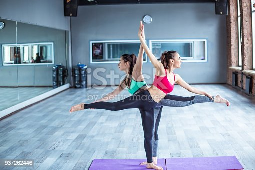 istock Yoga positions. Beautiful smiling women working out in gym together. Sport, yoga, healthy lifestyle 937262446