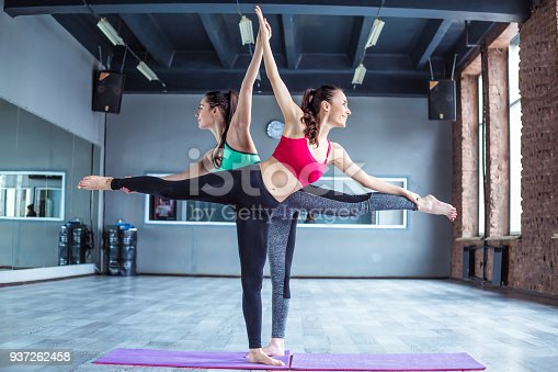 istock Yoga positions. Beautiful smiling women working out in gym together. Sport, yoga, healthy lifestyle 937262458