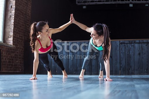 istock Yoga positions. Beautiful smiling women working out in gym together. Sport, yoga, healthy lifestyle 937262486