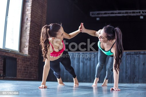 istock Yoga positions. Beautiful smiling women working out in gym together. Sport, yoga, healthy lifestyle 937262494