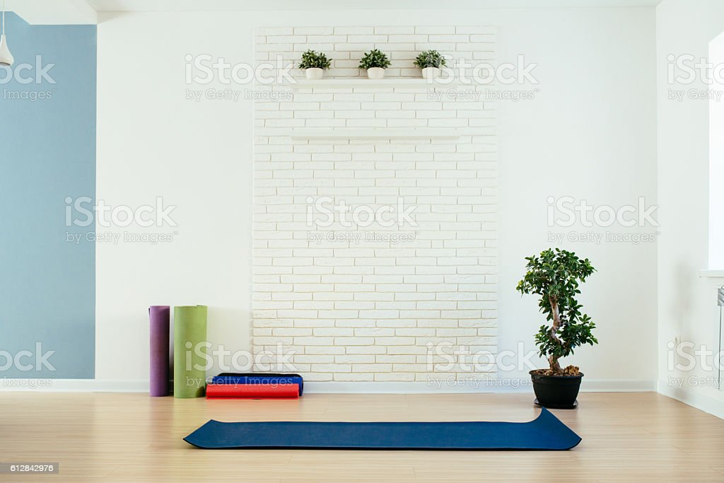 Yoga room with mat and white brick wall stock photo