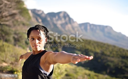 Shot of a fit young woman holding a warrior yoga pose in nature