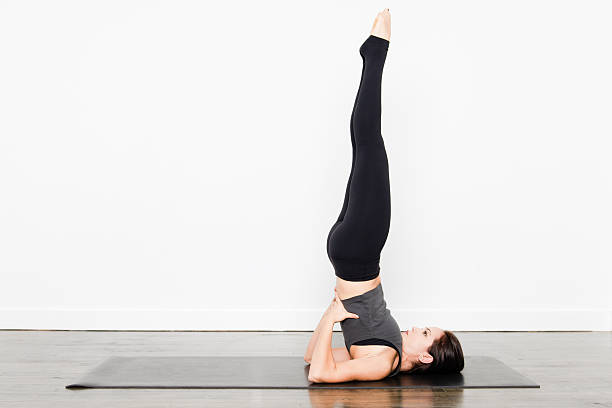 Yoga Series -  Supported Shoulderstand A young woman demonstrating various yoga poses. shoulder stand stock pictures, royalty-free photos & images