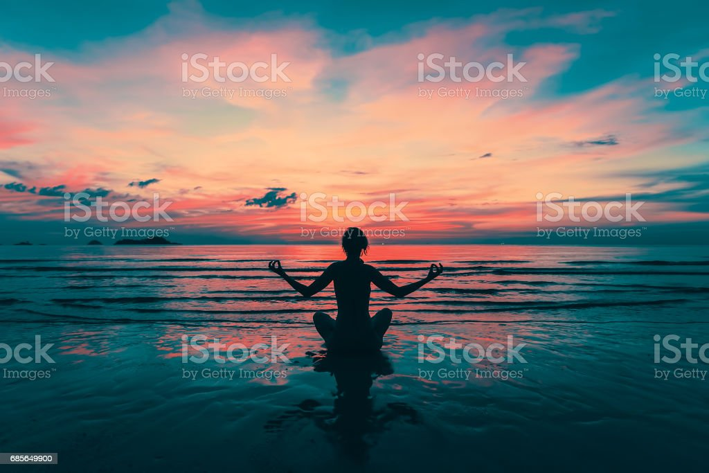 Yoga silhouette. Meditation girl on the sea during amazing sunset. Fitness and healthy lifestyle. ロイヤリティフリーストックフォト