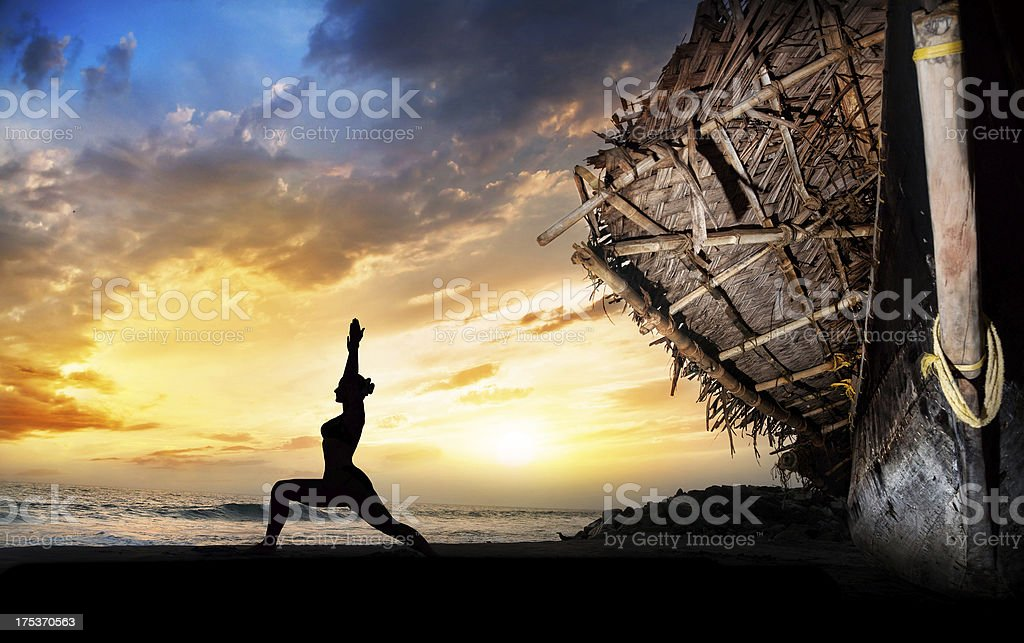 Yoga silhouette warrior pose near boat stock photo