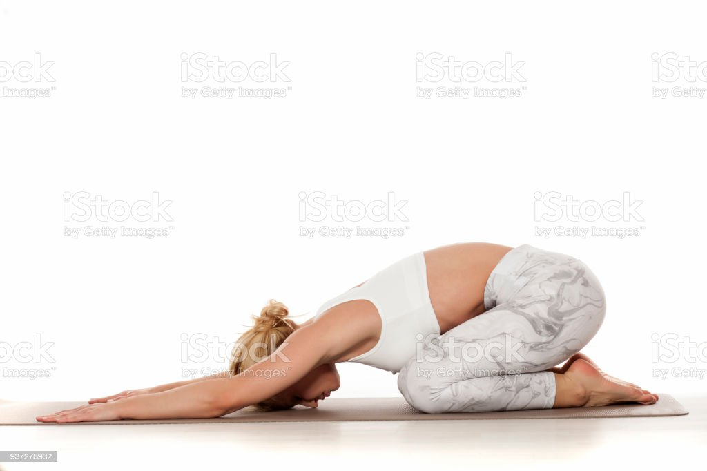 Yoga, sport, training and lifestyle concept - Young blonde woman doing yoga exercise. Portrait of young beautiful woman in white sportswear doing yoga practice stock photo