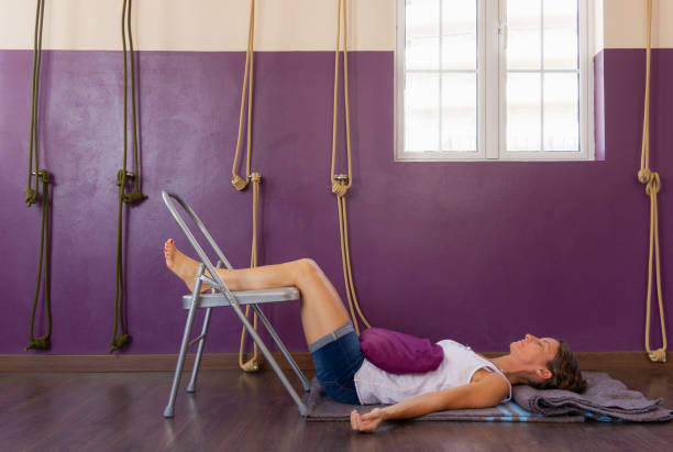 Yoga student rests on floor with legs up on chair at studio stock photo