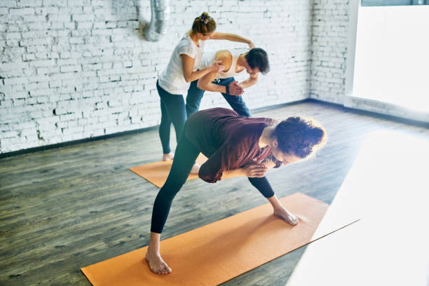 Yoga students under control of experienced coach stock photo