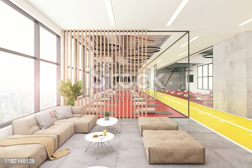 Yoga studio lobby interior with pastel colored sofa and pillows with big window, yellow floor and wooden wall with yoga room in the background. Template for copy space. Render.