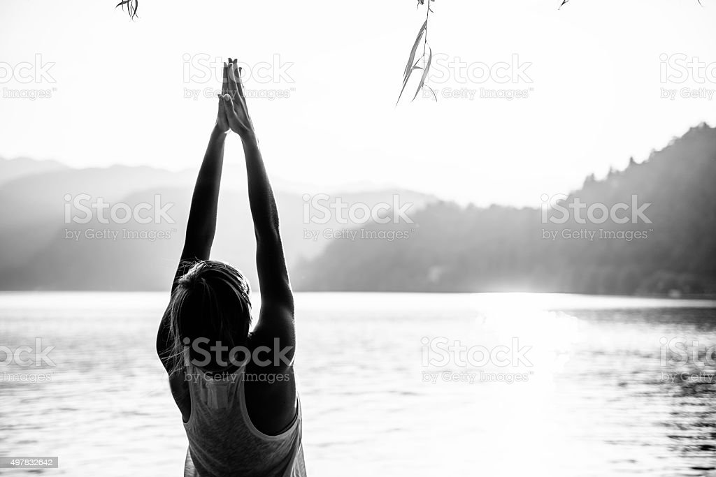 Yoga sun salutation, lake, upward salute, black and white stock photo