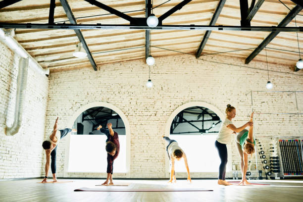 Yoga teacher correcting pose of students Careful yoga instructor assisting students to perform exercise at class yoga instructor stock pictures, royalty-free photos & images