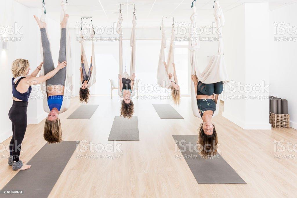 Yoga teacher guiding aerial yoga students stock photo