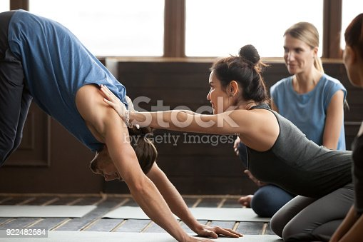 istock Yoga teacher helping man to stretch holding hands on shoulders 922482584