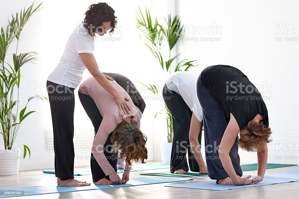 Yoga teacher helping others into the correct position stock photo