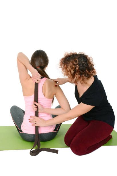Yoga teacher helping young girl to do yoga – zdjęcie