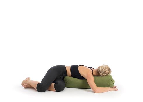 yoga teacher performing restorative yoga asana in white