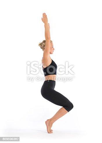 yoga teacher performing utkatasana chair pose fierce pose