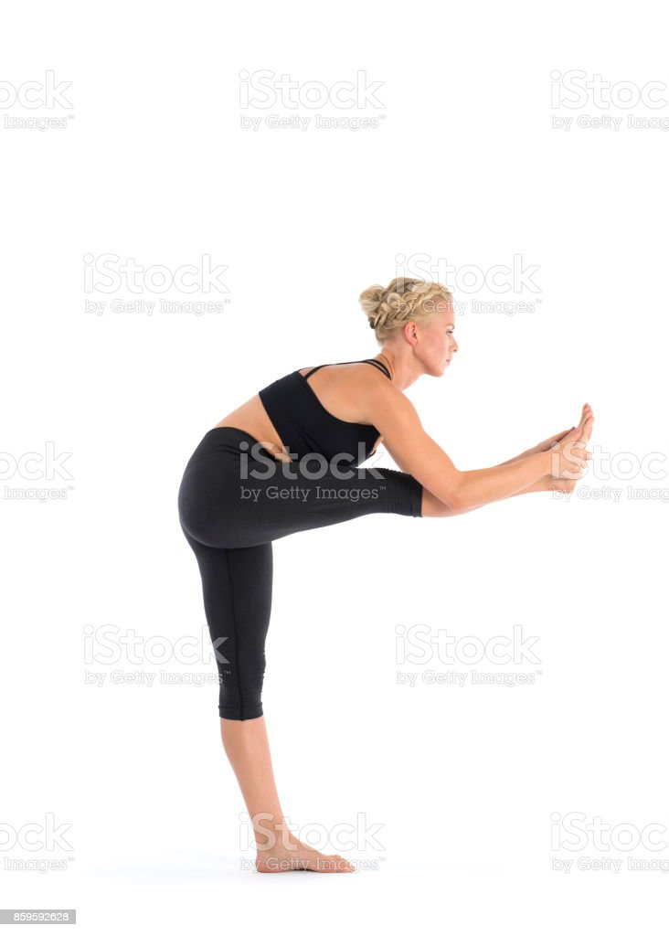 Yoga teacher performing Utthita Hasta Padangustha, Standing Hand to Big Toe Poseasana asana in white studio stock photo