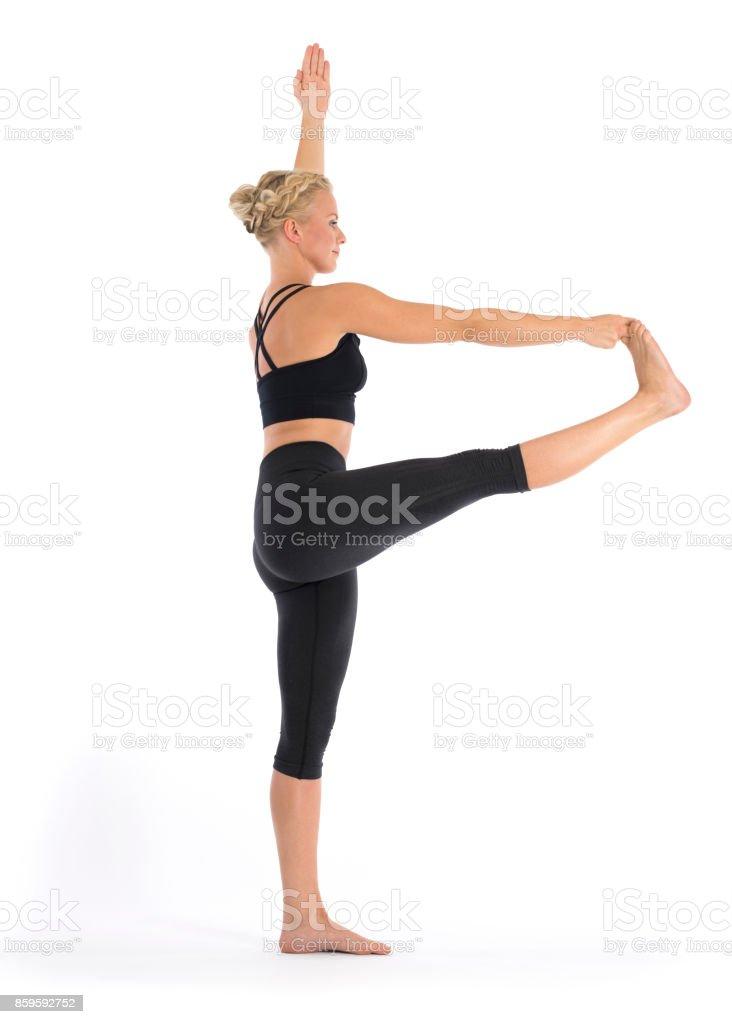 Yoga teacher performing Utthita Hasta Padangustha, Standing Hand to Big Toe Poseasana in white studio stock photo
