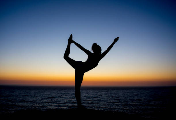yoga teacher posing at sunset at the beach with a silhouette back ground stock photo