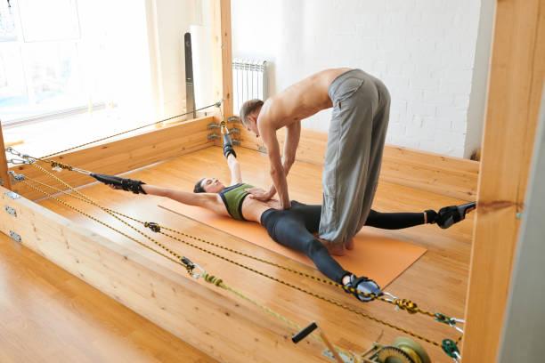 yoga-therapeuten tun behandlung massage frau auf yoga-trapez - trapez stock-fotos und bilder
