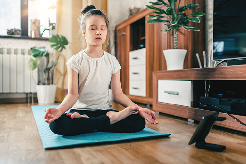Yoga training online. Cute girl at home with digital tablet watching fitness tutorials in lotus position