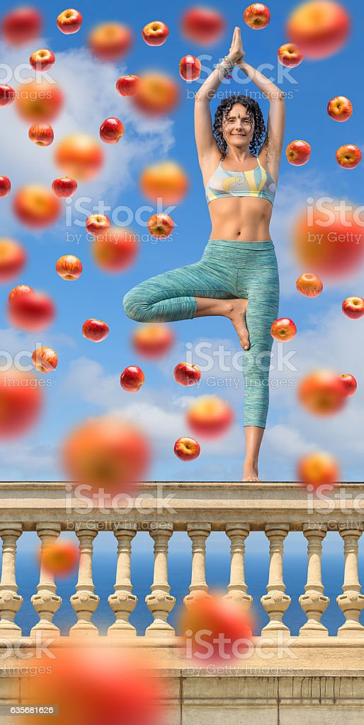 Yoga vegetarian woman posing with apples outdoors on balustrade