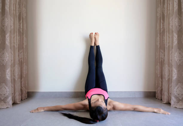 Yoga woman feet up relaxing on wall Yoga woman feet up relaxing in room on wall background AM stock pictures, royalty-free photos & images