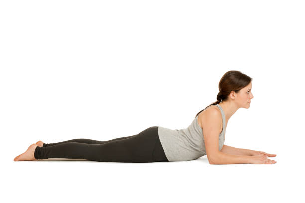 Yoga woman gray_Salamba Bhujangasana2 Side full body view of a young woman white background the Yoga position the Sphinx (Salamba Bhujangasana) showing in the home position. cobra pose stock pictures, royalty-free photos & images