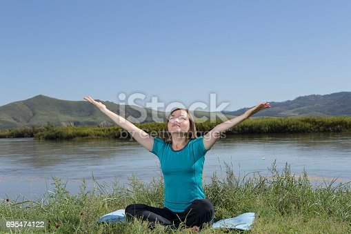 873786782 istock photo Yoga woman on nature background 695474122