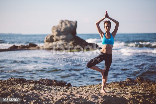 816941230 istock photo Yoga woman practicing yoga at the beach 958132932
