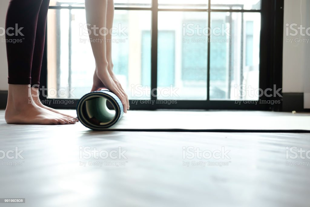 Yoga Woman rolling her lilac mat after a yoga class stock photo