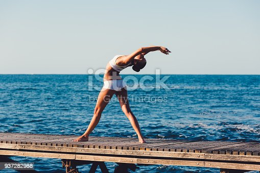 816941230istockphoto Yoga woman stretching at the seaside 937282988