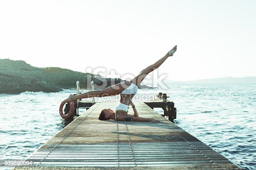 816941230istockphoto Yoga woman stretching at the seaside 939590094