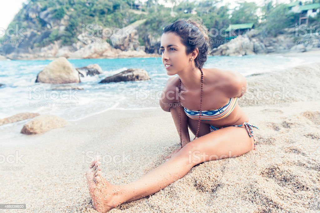 Yoga Woman with Flexible Body Stretches on Sandy Beach stock photo