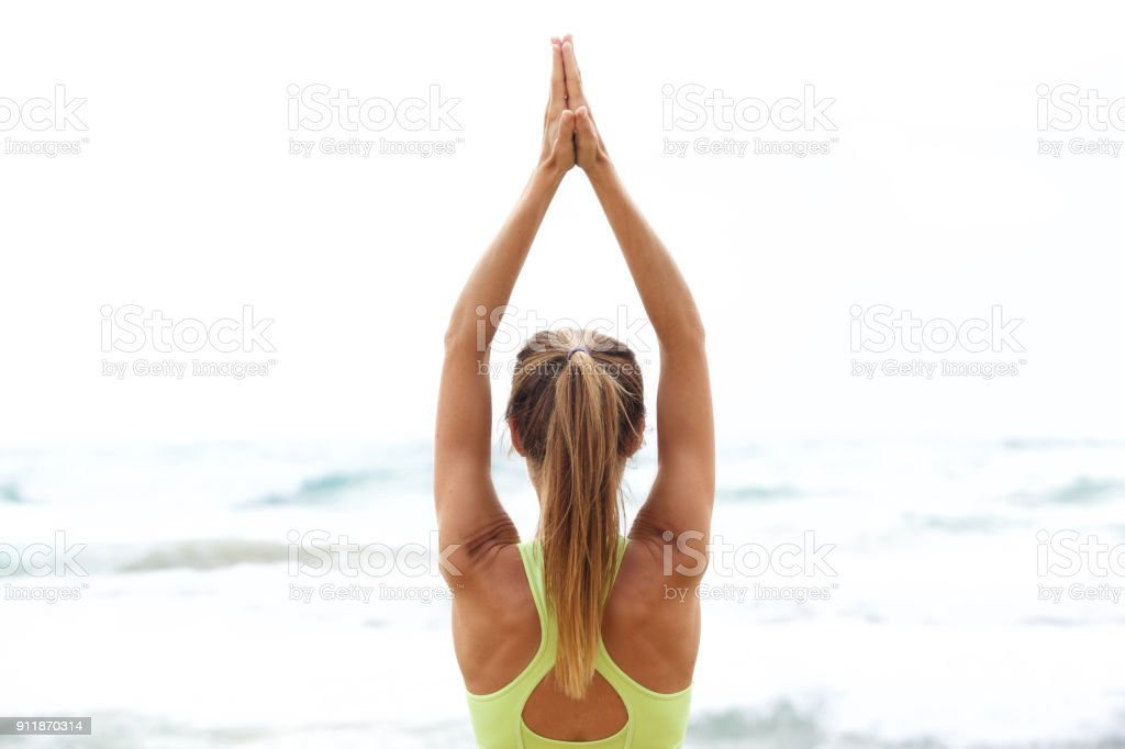 femme d'yoga avec les mains vers le haut par la mer - Photo