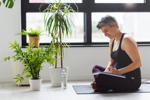 Yoga-Frau in ihrem Notebook persönliches Wachstum Resolutionen schreiben – Foto