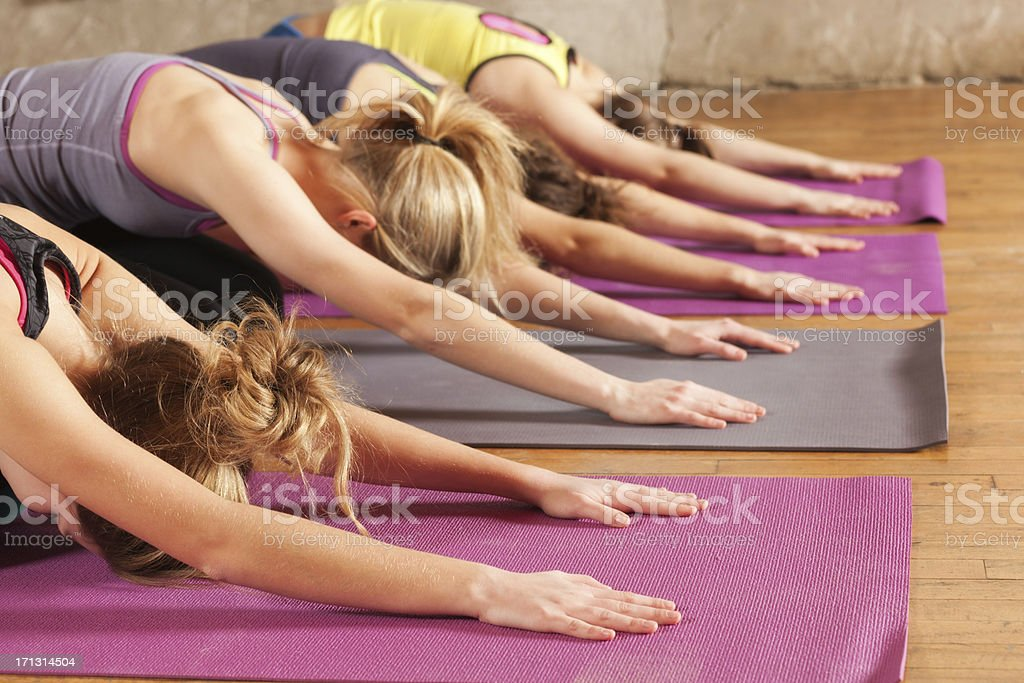 Yoga Workout Class, Group of Young Women Practicing Child Pose stock photo